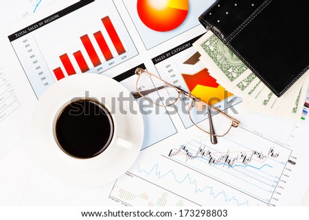 diary, glasses, a cup of coffee and business documents with charts, business still life