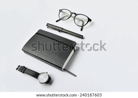 Diary, glasses, pen, and watch on white background