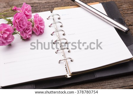 Diary note with pink rose on old wood (Organizer ,agenda, book, diary) - stock photo