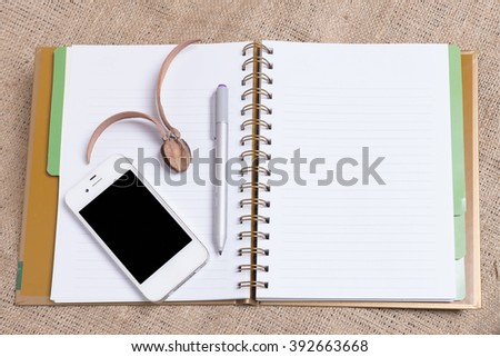 Diary note with smart phone on wood background (Organizer ,agenda, book, diary),,the screen of phone can change with clipping path - stock photo