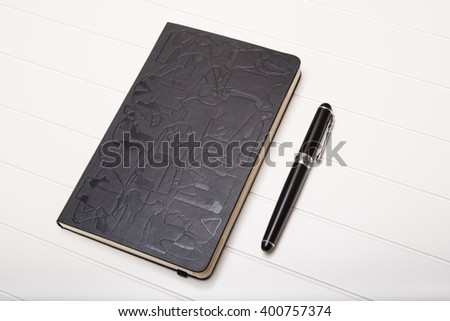 Diary notebook with leather cover and black vintage pen on a white table - stock photo