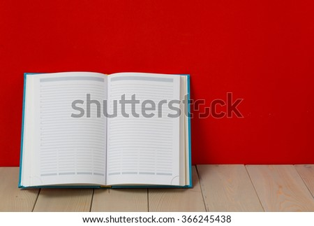 Diary on wooden deck table and red background.