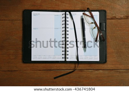 Diary planner book open calendar page with glasses and pen on the wooden desk - stock photo