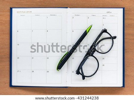 Diary planner book open  june calendar page with glasses and pen on the wooden desk - stock photo