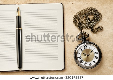 Diary with fountain pen and vintage pocket watch