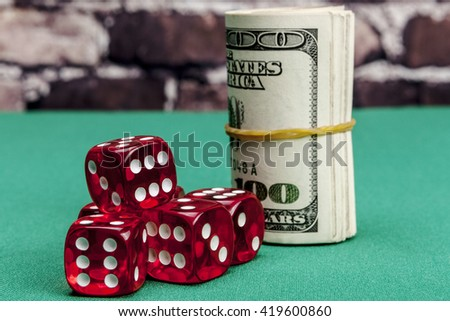 Dice and money on green table with shadow - stock photo