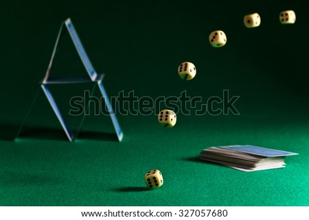 dice and playing cards on green table - stock photo