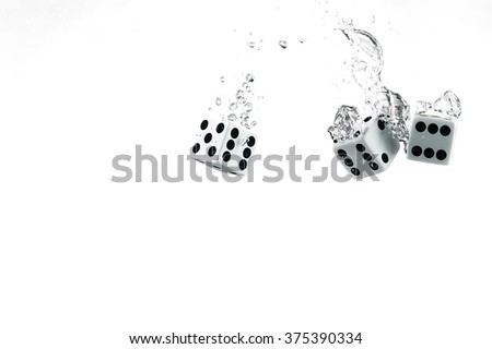 Dice dropped into the water, on a white background. Underwater game. Visible splash and air bubbles. - stock photo