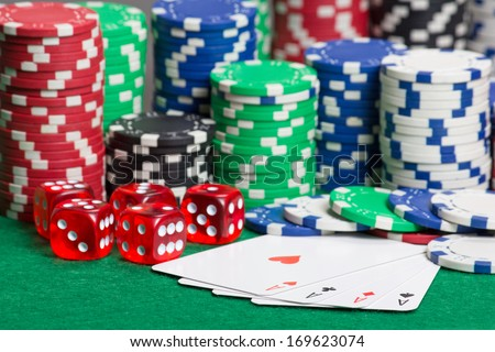 dice, four aces and colorful poker chips on a green table - stock photo