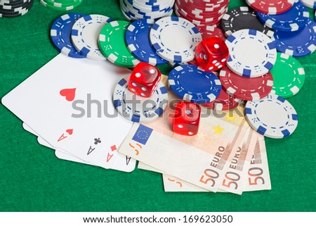 dice, four aces, colorful poker chips and euro banknotes on a green table