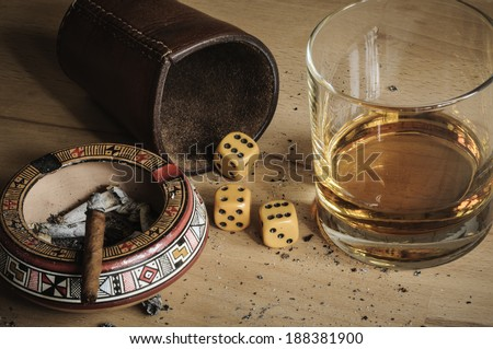 Dice game with cigar and alcoholic beverage. - stock photo