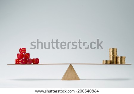 Dice stack and money coins balancing on a seesaw - stock photo