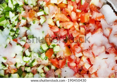 Dice the tomato and cucumber, pickle them with salt, and prepare for the salsa sauce. - stock photo