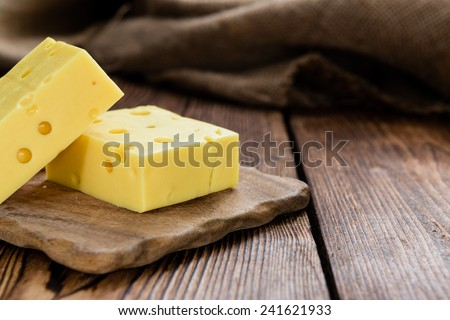 Diced Cheese (close-up shot) on rustic wooden background