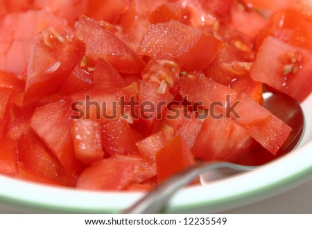 diced tomatoes in a bowl with a spoon