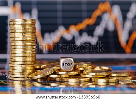 Dices cube with the word STOP golden coins and financial stock charts as background. Selective focus - stock photo