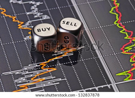 Dices cubes to trader. Cubes with the words SELL BUY on financial chart as background. Selective focus - stock photo