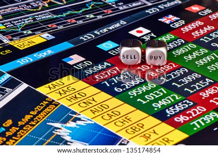 Dices cubes with the words SELL BUY and finances charts as background. Selective ficus - stock photo
