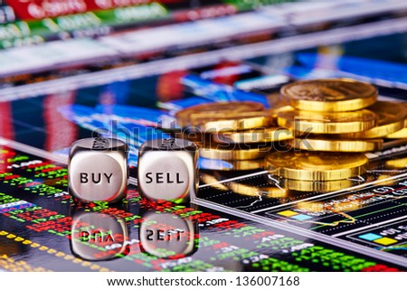 Dices cubes with the words SELL BUY, golden coins and financial chart with the columns of quotations as background. Selective focus - stock photo