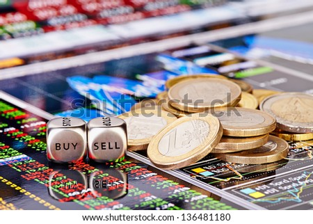 Dices cubes with the words SELL BUY, one-euro coins and a financial chart as the background. Selective focus - stock photo