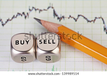 Dices cubes with the words SELL BUY, pencil and financial chart. Selective focus. - stock photo