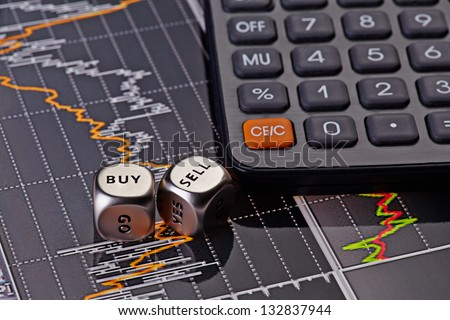 Dices cubes with words SELL BUY for trader and calculator. Financial chart as background. Selective focus - stock photo