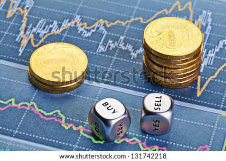Dices cubes with words SELL BUY,  stacks of coins and a up trend chart as the background. Successful trading. Selective focus - stock photo