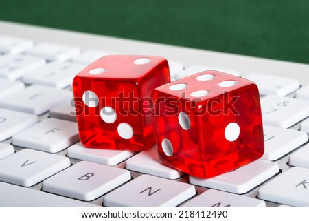 Dices on computer keyboard in online gambling concept - stock photo