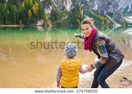 Did you see that? A mother in hiking gear smiling and pointing out to the lake. Seen from behind, her daughter is looking out at the lake and holding her mother's hand. Fall colours. - stock photo