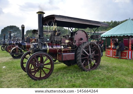 DIDCOT,OXFORDSHIRE,ENGLAND-JULY09-vintage steam traction engine with its owners on display in the show Woodcote Rally  a country fair on July 09,2011 in Didcot England