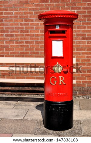 DIDCOT, UK - JULY 13. Preserved vintage British postal pillar box with gold crown and GR cypher cast into front on the old railway platform on July 13, 2013, at Didcot Railway Centre, Oxfordshire, UK. - stock photo