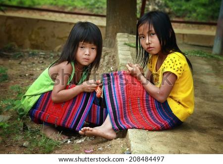 Dien Bien Phu, Dien Bien, Vietnam August 1, 2014: Two unidentified Hmong child is sitting under a tree.