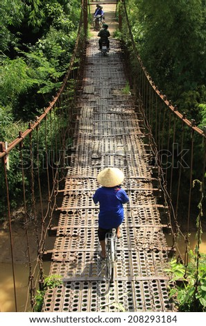 Dien Bien Phu, Vietnam July 31, 2014: Traffic on an old suspension bridge was built from the steel plate in Muong Thanh airport from the war the First Indochina.