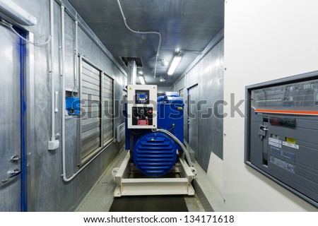 Diesel generator for backup power in room with control panel.. - stock photo