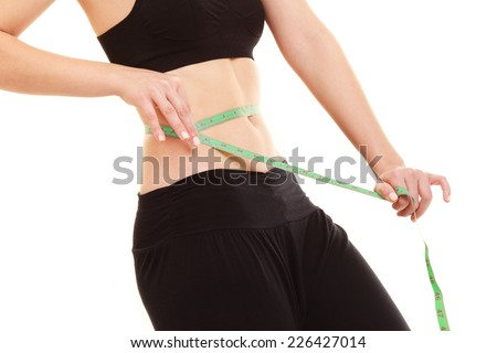 diet and healthy lifestyle. closeup of belly of slim fit girl young woman with green measure tape measuring her waist isolated on white - stock photo
