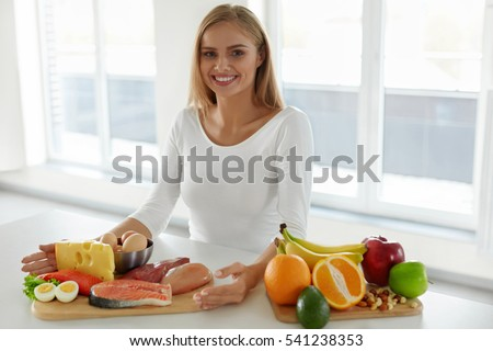 Diet And Nutrition. Beautiful Smiling Woman Sitting In Kitchen With Different Food Products And Ingredients On Table. Portrait Of Happy Healthy Girl With Variety Of Foods On Table. High Resolution