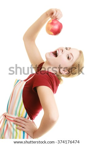 Diet and nutrition. Funny housewife or chef in striped kitchen apron eating red apple healthy fruit isolated