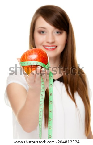 Diet and nutrition. Happy young woman holding apple fruit with measure tape isolated on white. Girl recommending healthy food. - stock photo