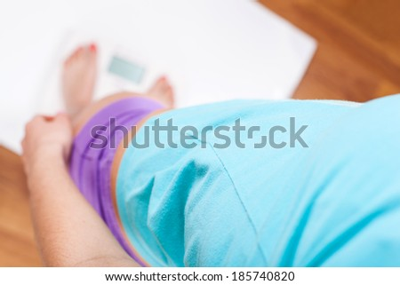 Diet and sport concept -  sporty woman on scale - stock photo