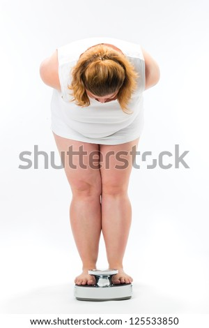 Diet and weight, fat young woman standing on a scale measuring her weight - stock photo