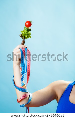 Diet and weight loss concept. Dietician woman hand with vegetarian food and colorful measuring tapes on blue background. - stock photo