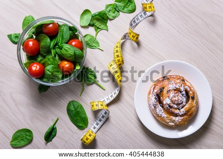 diet and weight loss concept - healthy salad with spinach and tomatoes, measure tape and sweet bun with raisins - stock photo