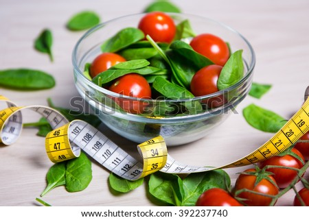diet and weight loss concept - salad with spinach and tomatoes and measure tape on wooden table background - stock photo
