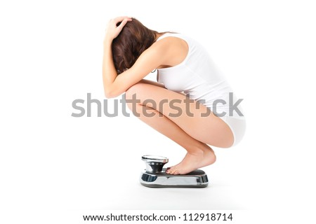 Diet and weight, young woman sitting on her haunches on a scale, she is desperate