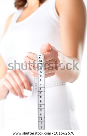 Diet and weight, young woman with a measuring tape for controlling her measure