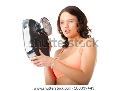 Diet and weight, young woman with a scale, she is desperate and threatening