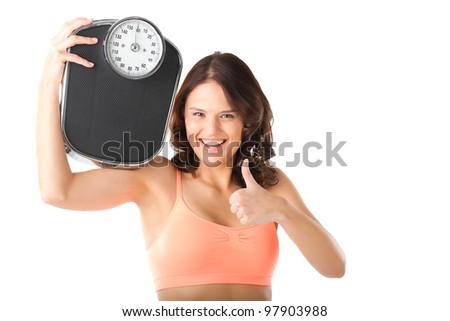 Diet and weight - young woman with a scale, she is happy about the success - stock photo