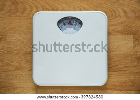 Diet bathroom weight foot scale on old wood background - stock photo