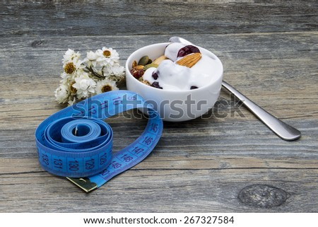 Diet breakfast with granola and yogurt on rustic wooden background. - stock photo
