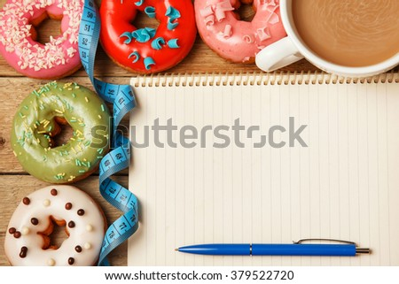 Diet concept. Colorful donuts and notepad